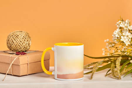 Colorful cup, cardboard box with skein of jute twine and bouquet of wild flowers on white tabletop against beige background. Close up, copy space