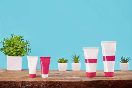 Four colorful no label different sized tubes on wooden tabletop against green plants in pots and turquoise background. Close up, copy space