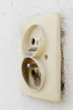plug in: burnt electrical plug in the wall