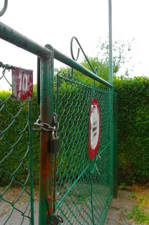 padlocked: padlocked metal gate with a road sign