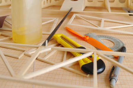 balsa: unfinished rc airplane with a tools on table