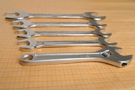 toolset: set of silver shiny spanners on the plotting paper in perspective view