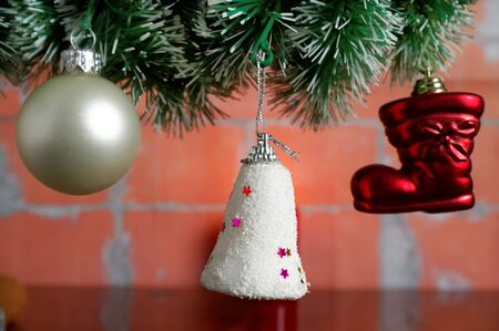 hanging christmas baubles on the artificial spruce twig against brick wall stock photo 66261603