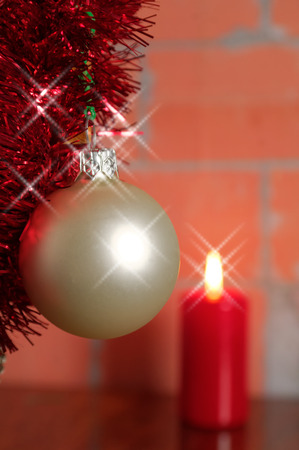 silver shiny hanging Christmas bauble against the burning candle Stock Photo