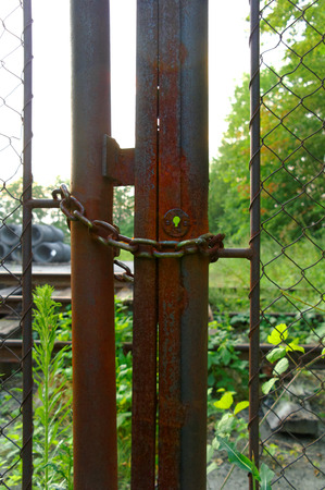 closeup of the old rusty gate with corroded chain