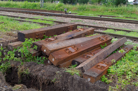stacked old used wooden sleepers beside the railway