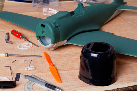 unfinished RC airplane, parts and tools on the workshop