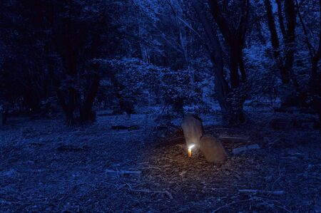 single burning candle on the old cemetery at the night 写真素材