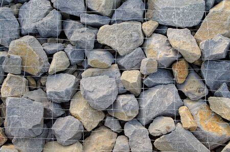 Pebbles covered by the silver shiny wire mesh