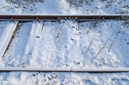 closeup of the snow covered rusty iron railroad