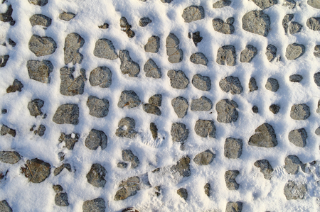 sidewalk made of cobblestone, partially covered by the snow