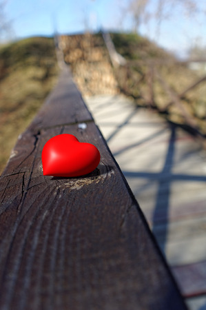 small red shiny heart on the long wooden handrail 写真素材