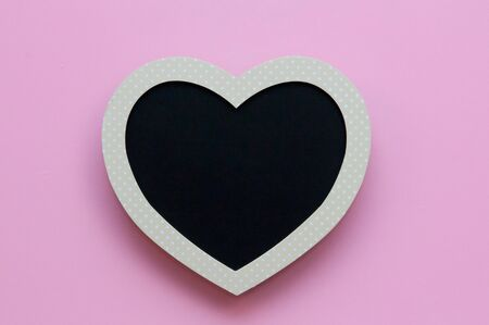 pink and black: Blank heart shaped black board on a pink background