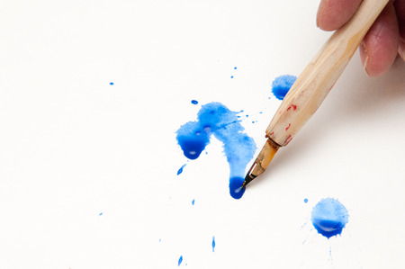 calligraphy pen: calligraphy pen with blue spilt ink on white paper