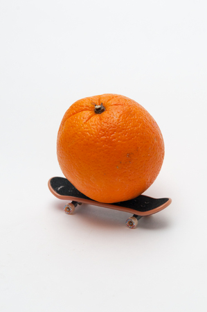 represent: Orange on a skateboard to represent sport and healthy living