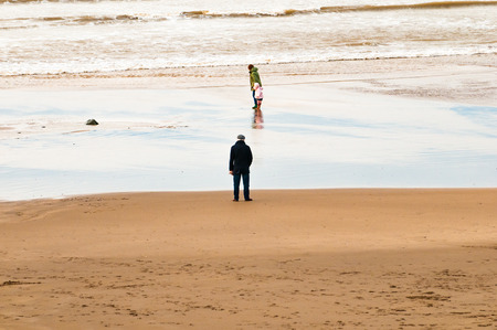 cold day: A child and grandparents play at the beach on a cold day Stock Photo