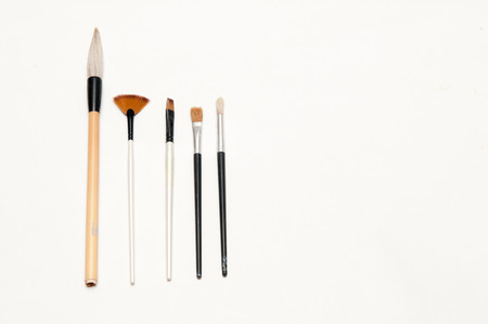 displayed: Artists brushes and pens displayed on isolated white background Stock Photo