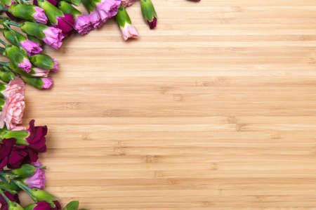 blank template: row of flowers with space for text on a wooden surface