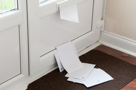 Unopened mail pilied up on the door mat
