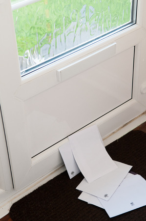 summons: Unopened mail pilied up on the door mat