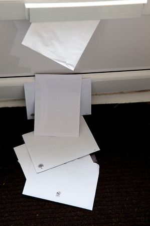unopened: Unopened mail pilied up on the door mat