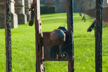 keep gate closed: Old gate locked with a rusty padlock