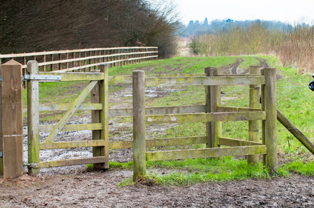open gate: Open gate to a muddy countryside path
