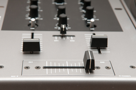 crossfader: Close up of a djs sound mixer for volume control