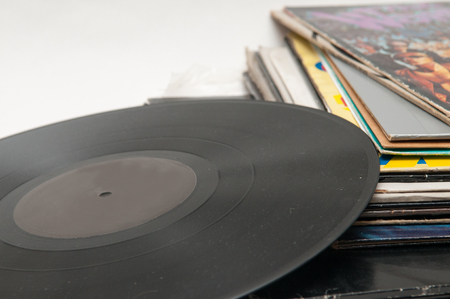 sleeve: selection of old vinyl records piled up with one out of the sleeve