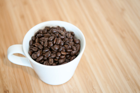caffiene: Strong flavoured coffee beans in a plain white mug