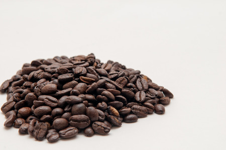 heaped: pile of coffee beans on a bright white background