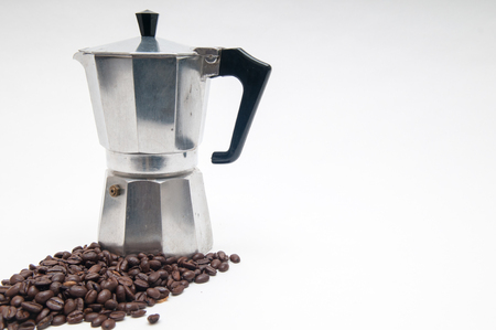 caffiene: coffee beans in the foreground with espresso maker Stock Photo