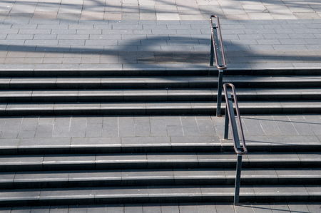 hand rails: concrete stairs in a city in the afternoon sun Stock Photo