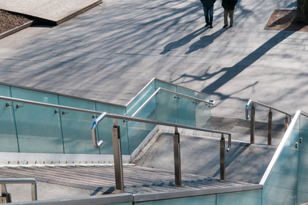 hand rail: View down steps to a bridge on a sunny day