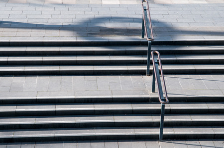 hand rail: concrete stairs in a city in the afternoon sun Stock Photo