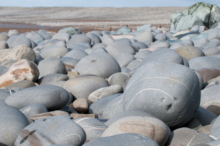 low angle views: Pebbles at the beach in the foreground of a coastal scene