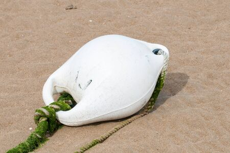 beach buoy: White buoy lying in the yellow sand of a beach Stock Photo