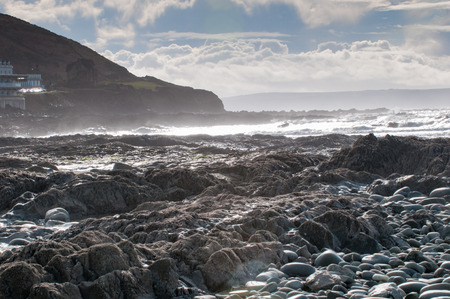 wide  wet: Rocky beach scene with sunlight reflecting on the sea Stock Photo