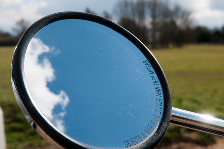 rear view mirror: Rear view mirror of a motorcycle with clouds in view