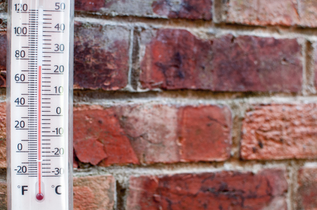 Thermometor measuring hot summer weather with a brick wall background Фото со стока