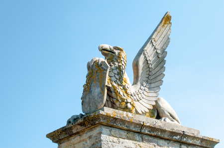 plinth: Statue of a winged mythical creature on a plinth holding a shield
