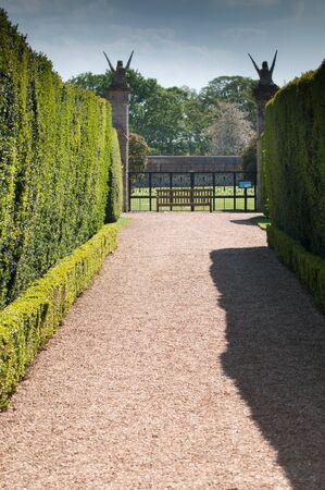 formal garden: Pathway through the grounds of a formal garden in natural daylight Stock Photo