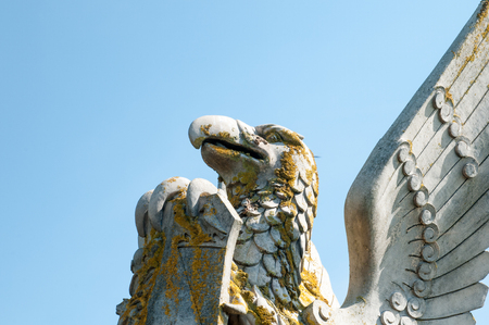 mythical: Statue of a winged mythical creature on a plinth holding a shield