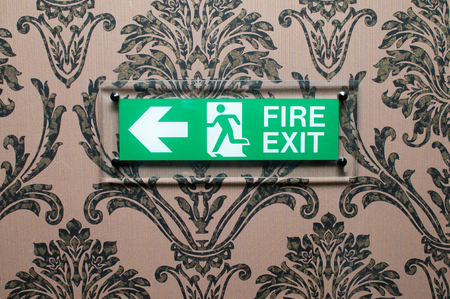 instruct: Green fire exit sign on a wallpapered hotel wall