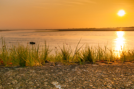 Sun rising over the water over the estuary leading to the ocean Stock Photo