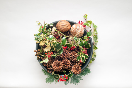 Festive Christmas decoration with holly and ivy on a white background and red ribbon at the base