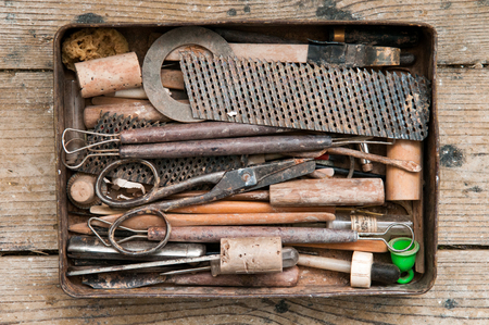 Vintage style tools in a retro tin tool box on a the workshop table Stock Photo