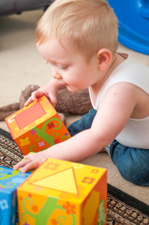 pre teen boy: baby playing with blocks to make a tower, happy baby boy Stock Photo