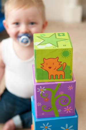 learning new skills: baby playing with blocks to make a tower, happy baby boy Stock Photo