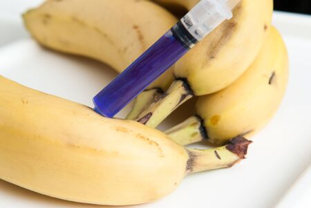 Gm food concept, additives and chemicals being injected into fruit